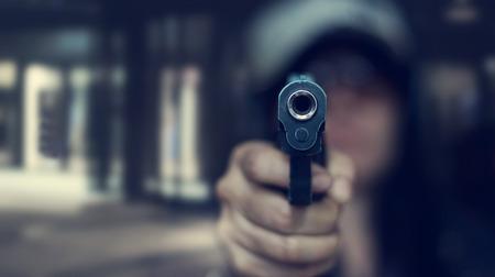 Vrouw die een kanon richt op het doel op donkere achtergrond, selectieve nadruk op voorkanon, uitstekende kleurentoon Stockfoto