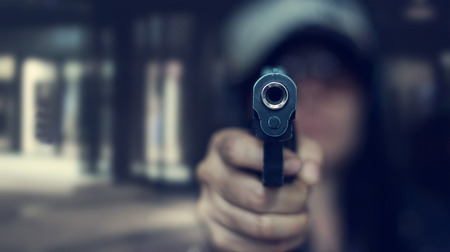 Woman pointing a gun at the target on dark background, selective focus on front gun, vintage color tone Imagens
