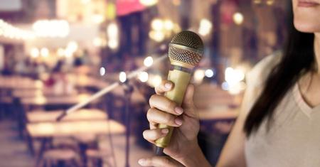 Vrouw met microfoon in de hand op pub en restaurant achtergrond Stockfoto