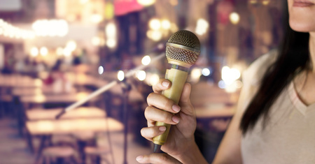 Woman holding microphone in hand on pub and restaurant background