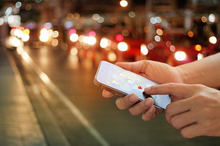 밤에 거리의 스마트 폰에서 내비게이션 앱을 사용하는 사람이 휴대 전화 화면에서 모두 디자인되었습니다.