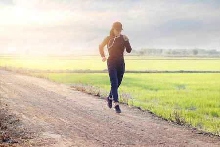 woman running excercise on rural road of green field sunset background