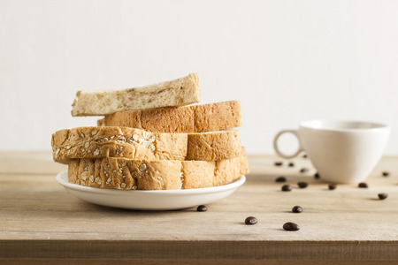 whole wheat toast: Wheat bread with white sesame, coffee beans and coffee cup on wooden table Stock Photo