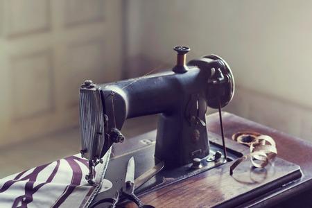 Vintage Nähmaschine mit Stoff und Schere im Zimmer, Vintage Farbton Standard-Bild