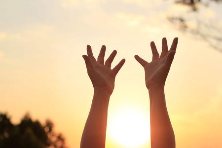Mujer manos rezando por la bendición de dios en la puesta de sol de fondo Foto de archivo