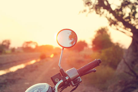 Rearview mirror of motorcycle on dirt road in countryside Stock Photo