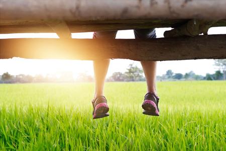 リラックスした女性の足は、朝の緑の水田の景色を楽しむ