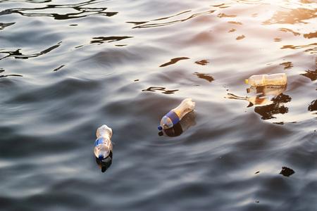Plastic huisvuil in de rivier op zonsondergang, verontreiniging en milieuconcept Stockfoto
