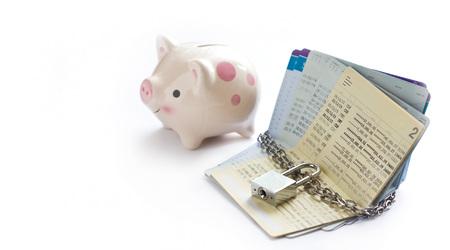 de rekeningbankboekjes werden gesloten door ketting en sleutel met spaarvarken op witte achtergrond, sparen en financieel concept Stockfoto