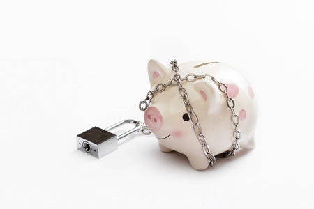 lock concept: Piggy banks is lock by chain and key on white background, saving and financial concept Stock Photo