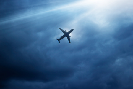 Airplane in the dark blue sky and cloud at strom