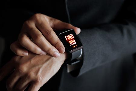 hand job: Businessman press button find job on smart watch in hand, dark background