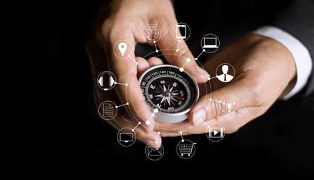 businessman using compass finding online shopping and icon customer network connection on dark background, m-banking and omni channel