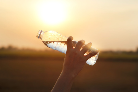 hand holding drinking water on sunset background