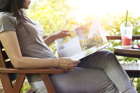 woman relaxing by reading travelling magazine and strawberry smoothie on table, nature background