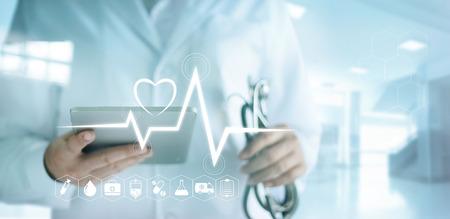 Arts met behulp van digitale tablet met medische pictogram en hartslag tarief in het ziekenhuis achtergrond