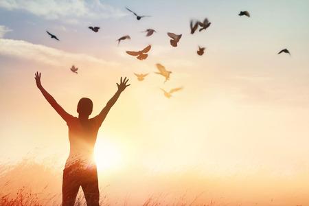 Mujer que ora y pájaro libre disfrutando de la naturaleza en el fondo la puesta del sol, el concepto de la esperanza Foto de archivo - 80150338