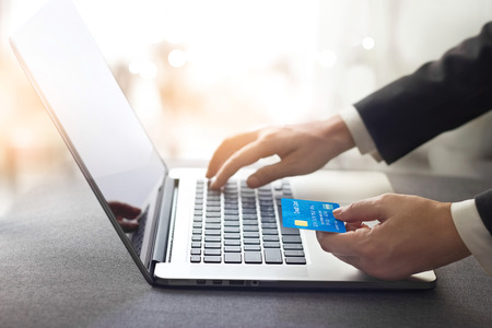 Hands of businessman holding credit card and using laptop, online shopping concept, all on credit card are design up. Stock Photo