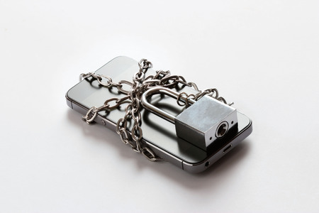 Smartphone with chain locked on white background, security and piracy network concept Banco de Imagens
