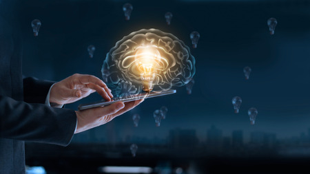 Glowing light bulb in brain over labtop of businessman among the others that not bright, its symbolic of creative and bright idea or leadership, innovation and creativity concept