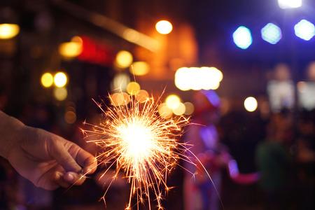 Man hand holding sparkler or firework on street night background
