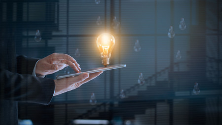 Glowing light bulb over labtop of businessman among the others that not bright, its symbolic of creative and bright idea or leadership, innovation and creativity concept