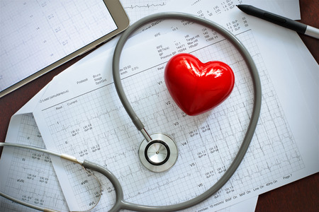 Stethoscope with red heart shape and annual heart health exam report, medical health care concept Archivio Fotografico