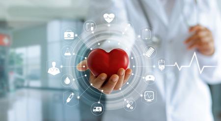 Médico de medicina com forma de coração vermelho na mão e ícone Conexão de rede médica com interface de tela virtual moderna, conceito de rede de tecnologia médica