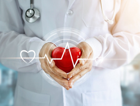 Doctor con estetoscopio y corazón rojo forma con icono latido del corazón en manos sobre fondo de hospital Foto de archivo - 82948100