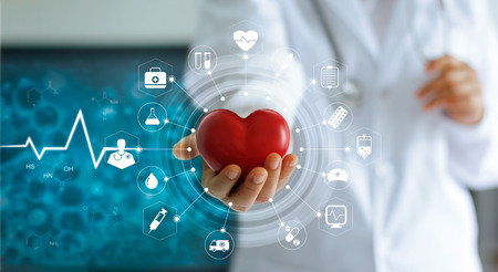 Medicine doctor holding red heart shape in hand and icon medical network connection with modern virtual screen interface in laboratory, medical technology network concept