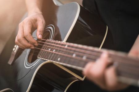 ギタープレーヤーは、アコースティックギターを演奏し、クローズアップ