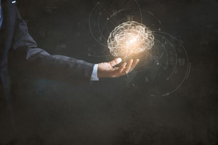 Empresario sosteniendo cerebro humano y la interfaz de usuario de negocios icono con la planificación de negocios cibernético en la textura de papel de fondo Foto de archivo - 85656906