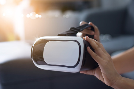 Man holding virtual reality goggles in outdoor background ,VR headset modern technology concept