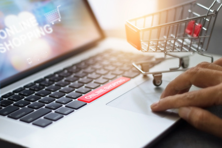 Shopping cart or trolley on laptop with text online shopping, network marketing business concept