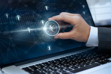 Businessman with a compass holding in hand and icon customer network connection on screen laptop background, m-banking and omni channel