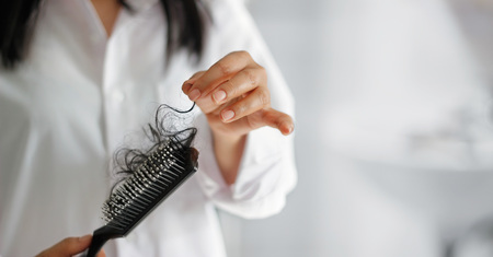 woman losing hair on hairbrush in hand, soft focus
