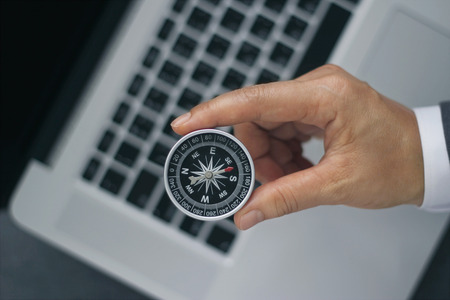 Businessman with a compass holding in hand on laptop background Reklamní fotografie