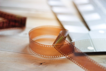 Movie clapper and film strip on a wooden background