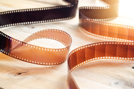 Movie film strips on wooden background