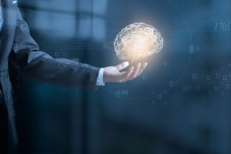 Businessman holding digital human brain and icon graphic in hand on dark blue background