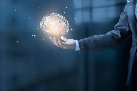 Businessman holding a brain and stardust in hand on blue office background