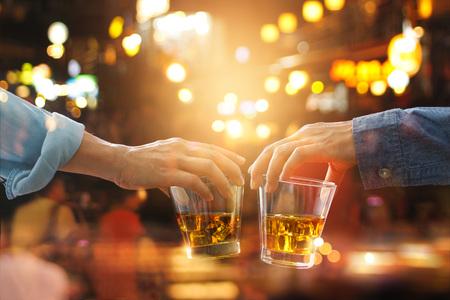 화려한 배경에서 작업 후 파티 밤에 버번 위스키 음료와 친구들 clinking 건배