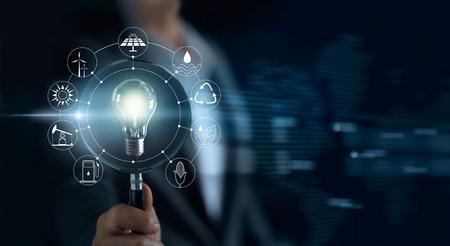 Homme tenant une loupe et une ampoule électrique, recherche de spectacles mondiaux montrant la consommation mondiale avec des icônes de sources d'énergie pour le développement durable et renouvelable. Concept d'écologie