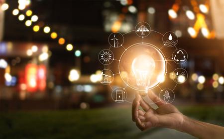 Mano que sostiene la bombilla frente a la demostración global del consumo mundial con iconos de fuentes de energía para el desarrollo sostenible y renovable. Concepto de Ecología Elementos de esta imagen proporcionada por la NASA. Foto de archivo