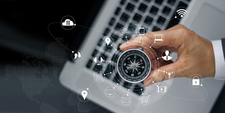 Businessman with a compass holding in hand on laptop and icon customer network connection on screen, m-banking and omni channel