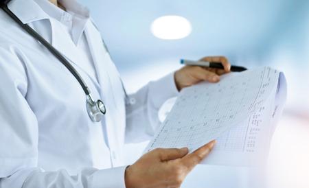 Ärztin, die heraus abhakt und Abschlußberichte im Raum eines Krankenhaushintergrundes liest