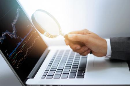 Geschäftsmann, der in der Hand Lupe, Suche von Börsedaten bezüglich des Laptopschirmes, Investmenthandelskonzept hält Standard-Bild