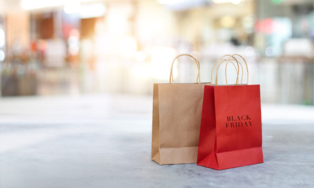 Black Friday shopping bags on the floor outdoors with the mall background Stock Photo