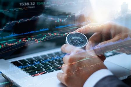 Het kompas van de zakenmanholding in handen, en gegevens die met het gebruiken van laptop effectenbeursgrafiek op het scherm, financiëngegevens en technologieconcept analyseren
