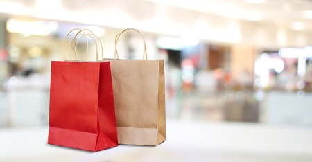 Red and brown shopping bags in mall store background, business, retail, banner concept Reklamní fotografie